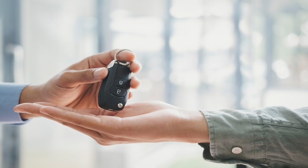 The Salesman Hand Giving Car Keys to the Buyer's Hand, After Selling Him Car.